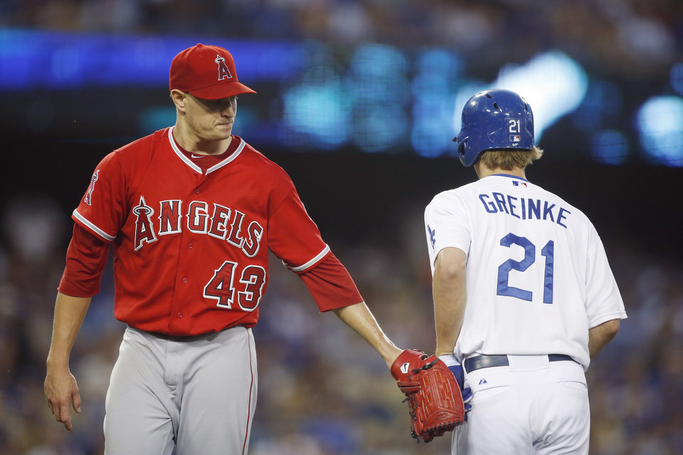 Photo - Los Angeles Angels starting pitcher Garrett Richards, left, taps Los Angeles Dodgers starting pitcher Zack Greinke, right with his glove after Greinke flied out to end the second inning of a baseball game, Monday, August 4, 2014, in Los Angeles. (AP Photo/Danny Moloshok)