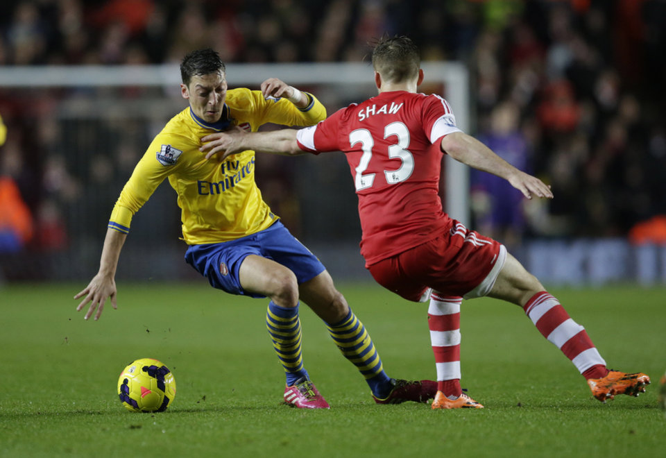 Photo - Southampton's Luke Shaw, right, competes for the ball with Arsenal's Mesut Ozil during the English Premier League soccer match between Southampton and Arsenal at St Mary's stadium in Southampton, Tuesday, Jan. 28, 2014.  (AP Photo/Matt Dunham)