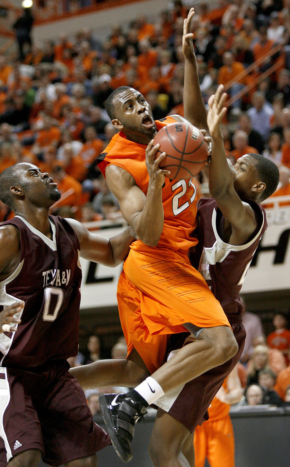 Photo - OSU's James Anderson goes to the basket between Texas A&M's Bryan Davis, left, and Khris Middleton during an NCAA college basketball game between the Oklahoma State University and Texas A&M at Gallagher-Iba Arena in Stillwater, Okla., Wednesday, January 27, 2010. Photo by Bryan Terry, The Oklahoman