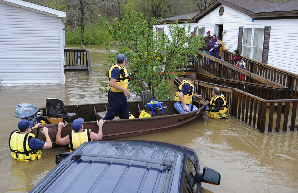 Photo - Firefighters rescue a family from their home, surrounded by floodwaters, in a mobile home park in Pelham, Ala., on Monday, April 6, 2014. Overnight storms dumped torrential rains in central Alabama, causing flooding across a wide area. (AP Photo/Jay Reeves)