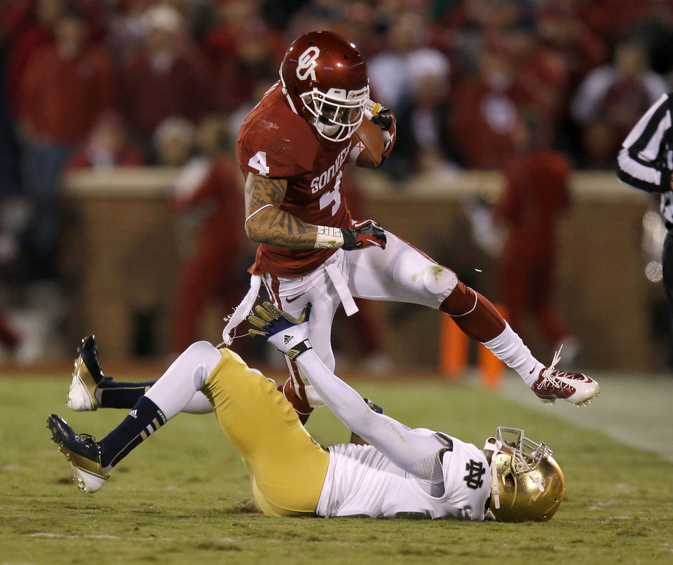 Photo - OU's Kenny Stills (4) leaps over Notre Dame's KeiVarae Russell (6) during the college football game between the University of Oklahoma Sooners (OU) and the Notre Dame Fighting Irish at Gaylord Family-Oklahoma Memorial Stadium in Norman, Okla., Saturday, Oct. 27, 2012. Photo by Bryan Terry, The Oklahoman