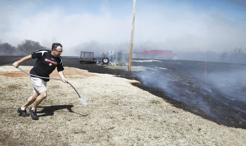 Photo - Matt Orr rushes to stop a large grass fire near his rural home on Friday, March 11, 2011, in Goldsby, Okla. Photo by Steve Sisney, The Oklahoman