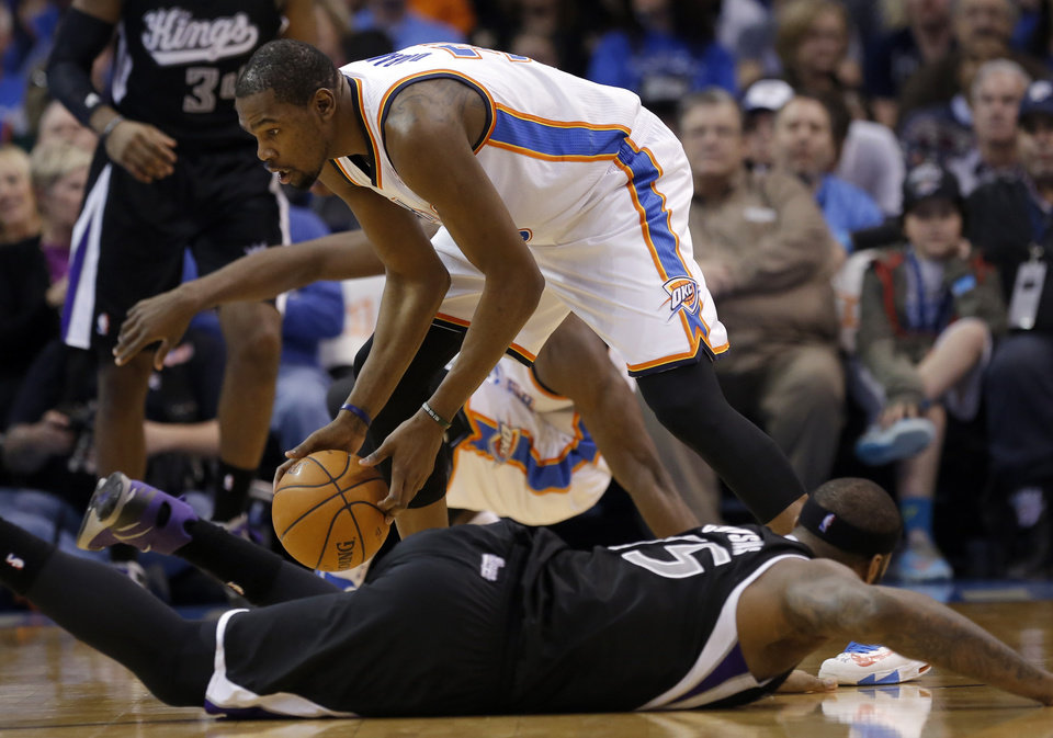 Photo - Oklahoma City's Kevin Durant (35) traps a loose ball from Sacramento's DeMarcus Cousins (15) during the NBA game between the Oklahoma City Thunder and the Sacramento Kings at the Chesapeake Energy Arena, Sunday, Jan. 19, 2014.  Photo by Sarah Phipps, The Oklahoman