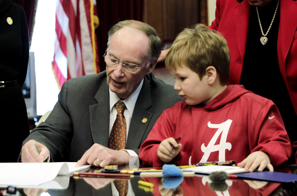 Photo - In this photo provided by the Governor's office, Gov. Robert Bentley, left, draws with 6-year-old Ethan Gilman during a visit to the Governor's Office in Montgomery, Ala. on Wednesday, Feb. 13, 2012. Ethan was held hostage in an underground bunker in a near week-long standoff in Midland City, Ala. (AP Photo/Alabama Governor's Office, Jamie Martin)