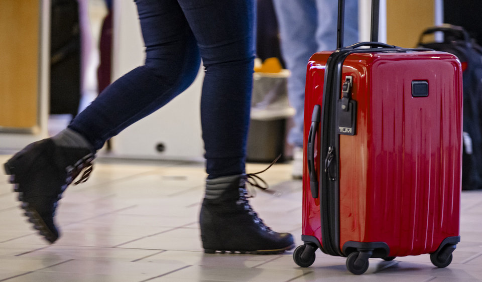 Photo - A traveler pushes a piece of luggage while making their way though Will Rogers World Airport in Oklahoma City, Okla. on Friday, March 13, 2020.    [Chris Landsberger/The Oklahoman]