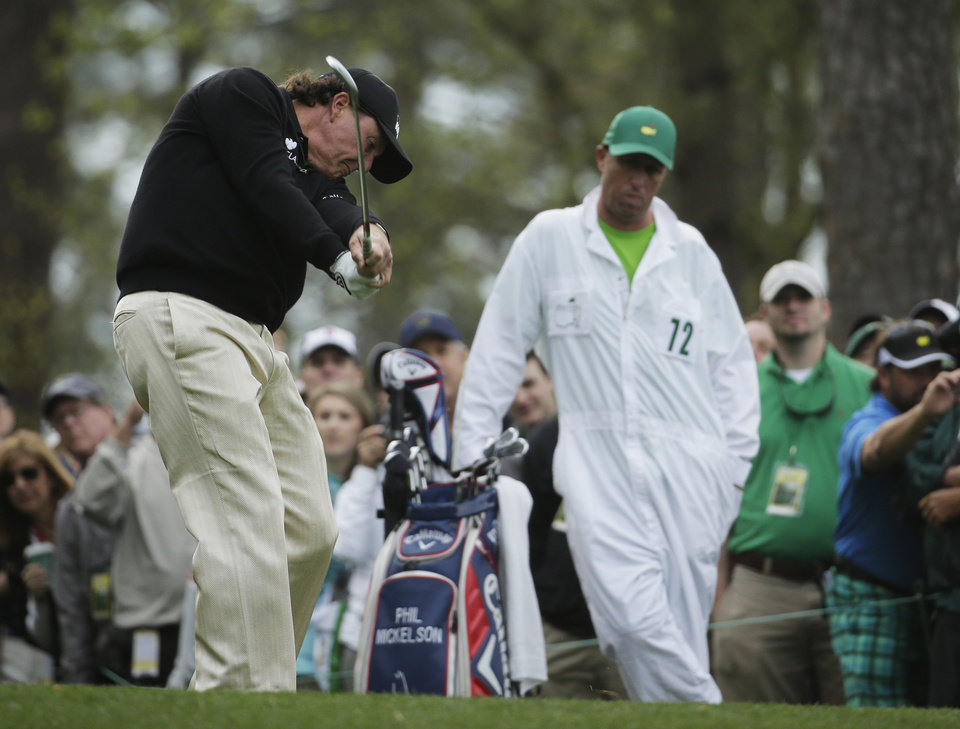 Photo - Caddy Jim MacKay, right, watches as Phil Mickelson tee off on the fourth hole during a practice round for the Masters golf tournament Tuesday, April 8, 2014, in Augusta, Ga. (AP Photo/Chris Carlson)