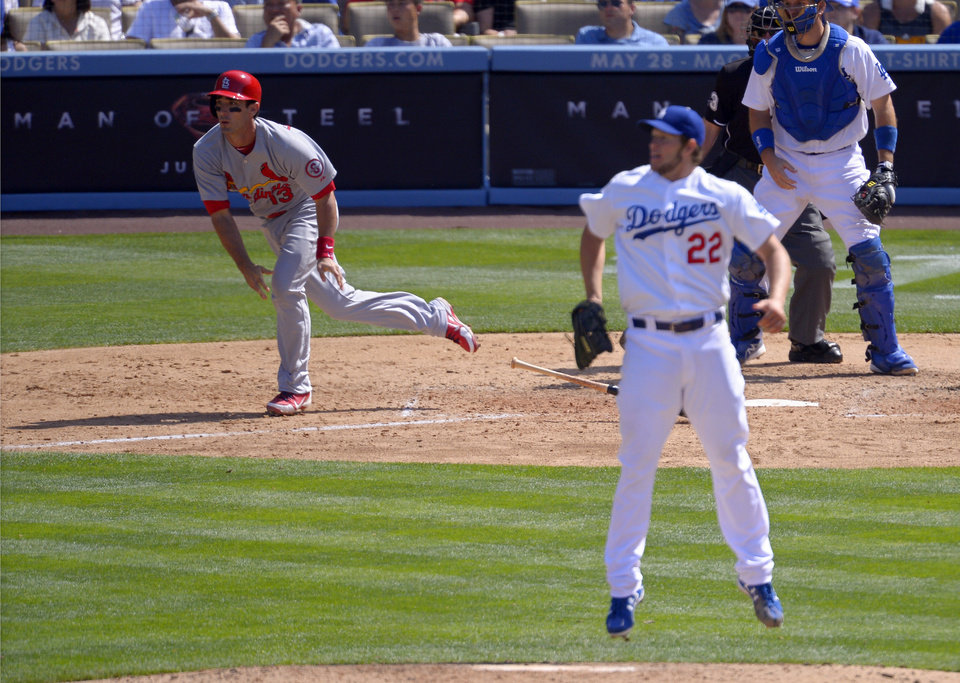 St. Louis Cardinals' Matt Carpenter, left, hits an RBI-single as Los Angeles Dodgers starting pitcher Clayton Kershaw (22) jumps and catcher A.J. Ellis looks on during the seventh inning of a baseball game on Sunday, May 26, 2013, in Los Angeles.  (AP Photo/Mark J. Terrill)