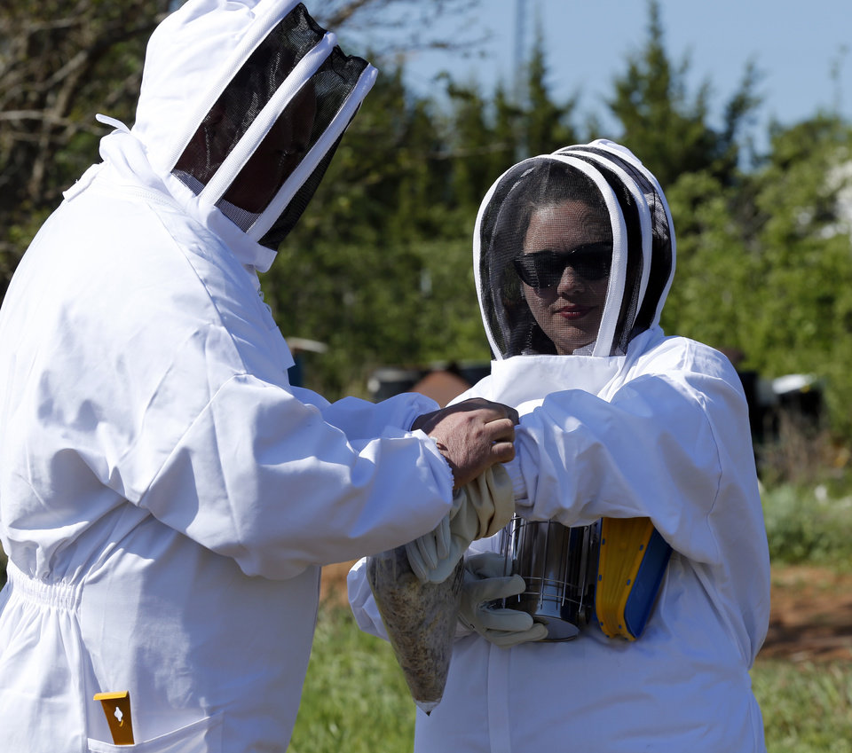 New beekeepers Matt and Michelle Stringer adjust their protective gear on Saturday, May 4, 2013, in Norman, Okla.  