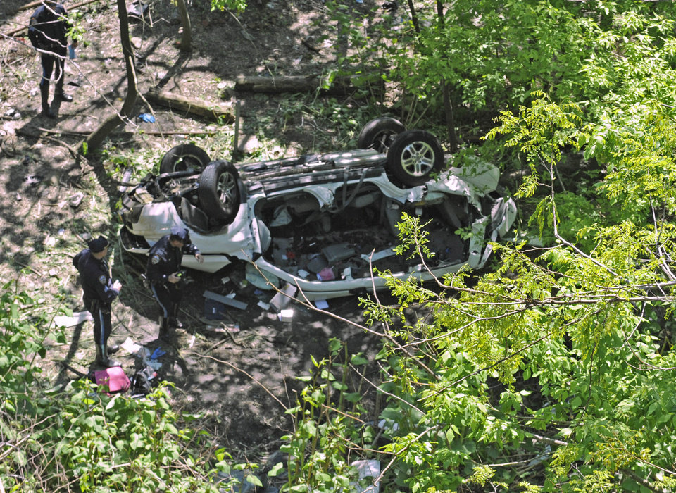 Photo -   FILE - In this April 29, 2012 file photo, police investigate an accident that wiped out three generations of a Bronx family, in New York. Seven people died, including three children, when the family's SUV hit a median on the Bronx River Parkway, veered off a bridge and fell onto the grounds of the Bronx Zoo. The fatal incident is being touted by some transportation advocates as more evidence that New York City's aging highway system needs major upgrades. (AP Photo/ Louis Lanzano, File)