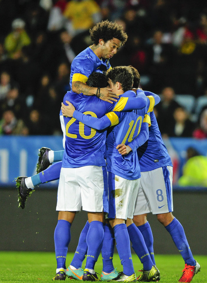 Brazil's Oscar (19) celebrates with team mates Hulk, Marcelo (on top) and Kaká after Oscar goal, the first goal of the game, during the international friendly soccer match at Swedbank Stadium in Malmo, Sweden, Thursday Oct. 11, 2012. (AP photo / Scanpix Sweden / Bjorn Lindgren) SWEDEN OUT