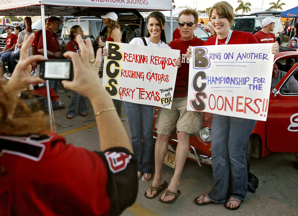 Photo - Sooner fans Alex Eppler, Rick Perry and Jordan Eppler, from left, pose for photos before the BCS National Championship college football game between the University of Oklahoma Sooners (OU) and the University of Florida Gators (UF) on Thursday, Jan. 8, 2009, at Dolphin Stadium in Miami Gardens, Fla. 