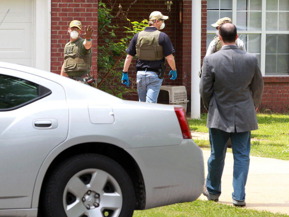 Photo - An FBI agent stops homeowner James E. Dutschke from approaching his home Tuesday, April 23, 2013, in Tupelo, Miss.    The agents begin to serach his home in connection with the ricin letters sent to  Sen. Roger Wicker and President Barack Obama.(AP Photo/Northeast Mississippi Daily Journal, Thomas Wells)  MANDATORY CREDIT
