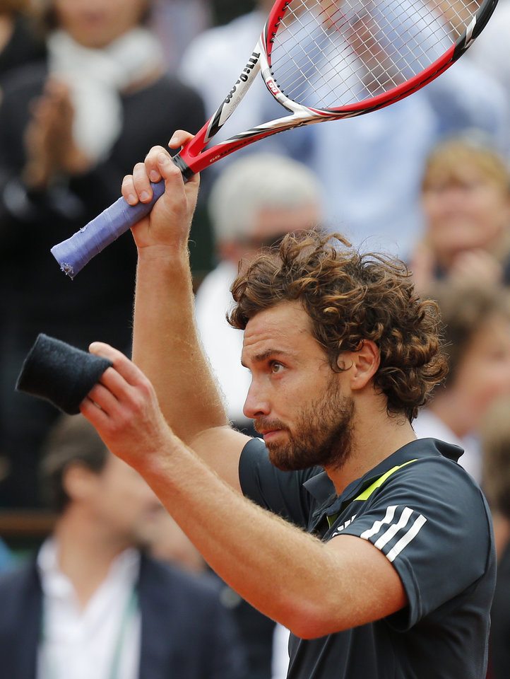 Photo - Latvia's Ernests Gulbis waves after defeating Switzerland's Roger Federer during their fourth round match of  the French Open tennis tournament at the Roland Garros stadium, in Paris, France, Sunday, June 1, 2014. (AP Photo/David Vincent)