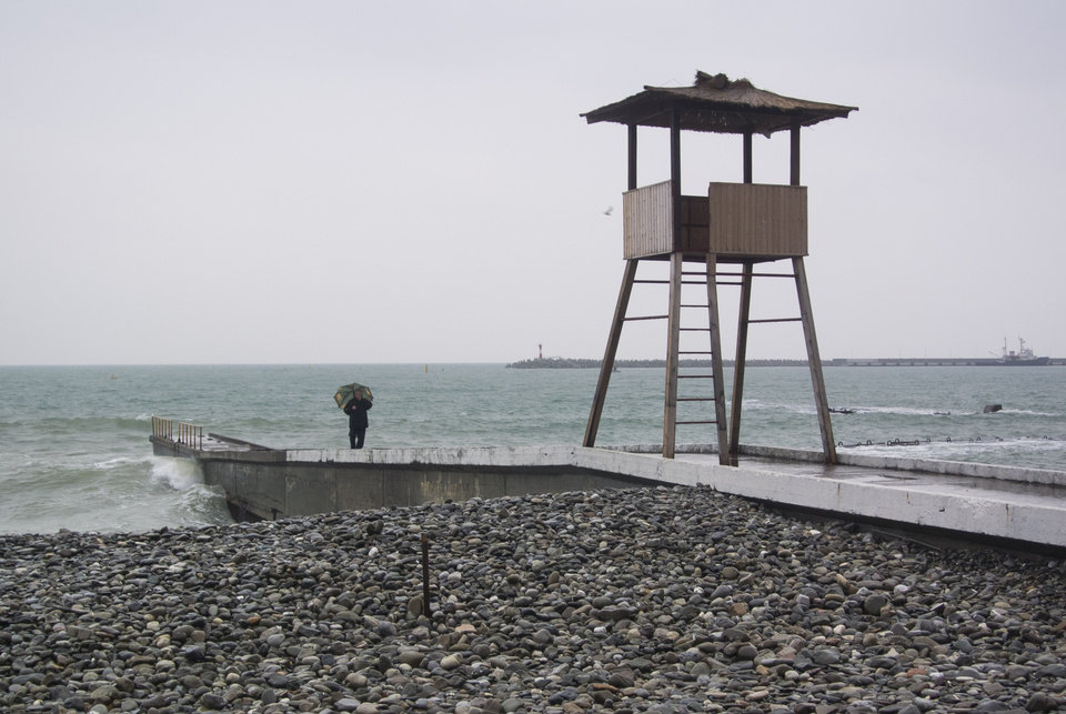 Photo - In this photo taken Thursday, Jan. 23, 2014 a man with an umbrella walks on the pier in central Sochi, Russia. The Russian Black Sea resort of Sochi is hosting the Winter Games on Feb. 7-23.  (AP Photo/Nataliya Vasilyeva)