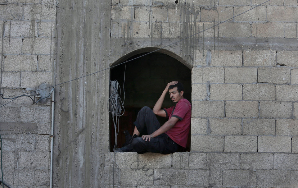 Photo - A Palestinian looks at a destroyed house after an Israeli missile strike in Khan Younis, Gaza Strip, Tuesday, July 8, 2014. The Israeli military launched what could be a long-term offensive against the Hamas-ruled Gaza Strip on Tuesday, striking sites in Gaza and mobilizing troops for a possible ground invasion aimed at stopping a heavy barrage of rocket attacks against Israel. (AP Photo/Khalil Hamra)