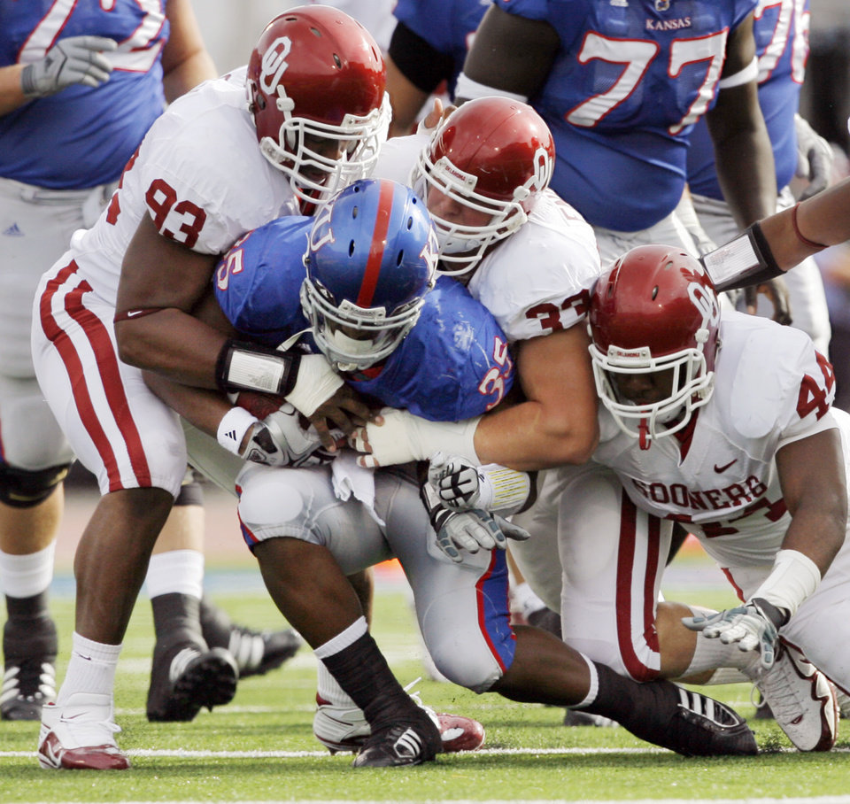 Photo - OU defenders, from left, Gerald McCoy (93), Autson English (33) and Jeremy Beal (44) stop KU's Toben Opurum (35) on a carry during the first half of the college football game between the University of Oklahoma Sooners (OU) and the University of Kansas Jayhawks (KU) on Saturday, Oct. 24, 2009, in Lawrence, Kan. OU won, 35-13. Photo by Nate Billings, The Oklahoman