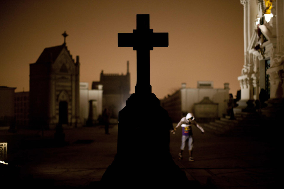 In this Nov.10, 2012 photo, a cross stands in the Presbitero Matias Maestro cemetery during a nighttime guided tour in Lima, Peru. The cemetery, created by one of the last Spanish viceroys, was established the outside the walls of old Lima. There are no more burials anymore at the cemetery unless a family owns a mausoleum. (AP Photo/Rodrigo Abd)
