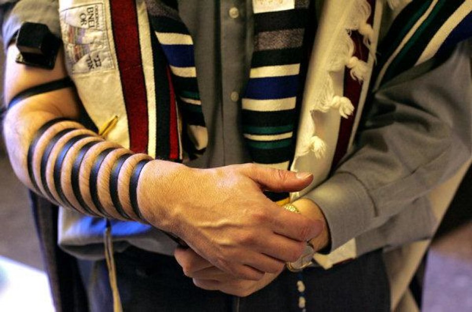 Photo - Rabbi Russell Fox shows members of Emanuel Synagogue how to put on tefillin in this 2008 photo. Photo by John Clanton, The Oklahoman Archive.    JOHN CLANTON - THE OKLAHOMAN