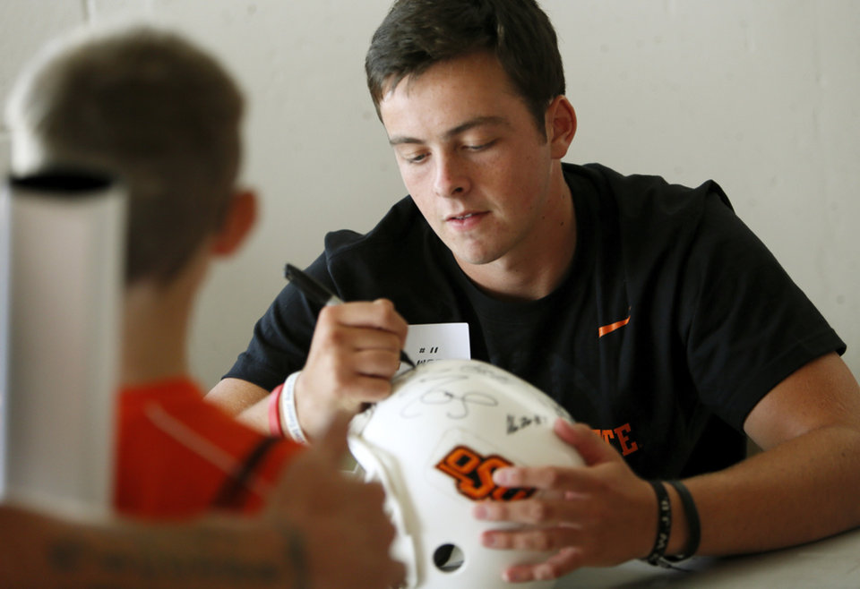 Photo - OSU quarterback Wes Lunt autographs a helmet during OSU Fan Appreciation Day at Gallagher-Iba Arena in Stillwater, Okla., Saturday, Aug. 4, 2012. Photo by Nate Billings, The Oklahoman