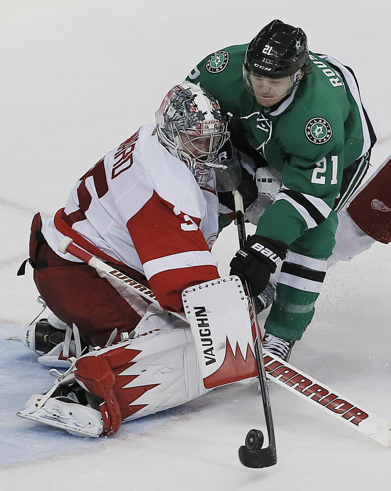 Photo - Dallas Stars forward Antoine Roussel (21) attempts a shot as Detroit Red Wings goalie Jimmy Howard (35) defends in the first period of an NHL hockey game, Saturday, Jan. 4, 2014, in Dallas. Roussel was called for interference on the play. (AP Photo/Brandon Wade)