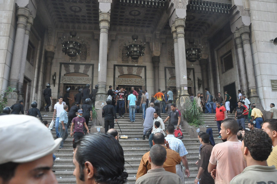 Photo - A group of Egyptians gather at the al-Fatah mosque, after hundreds of Muslim Brotherhood supporters barricaded themselves inside the mosque overnight, following a day of fierce street battles that left scores of people dead, near Ramses Square in downtown Cairo, Egypt, Saturday, Aug. 17, 2013. Authorities say police in Cairo are negotiating with people barricaded in a mosque and promising them safe passage if they leave. Muslim Brotherhood supporters of Egypt's ousted Islamist president are vowing to defy a state of emergency with new protests today, adding to the tension. (AP Photo/Hussein Tallal)