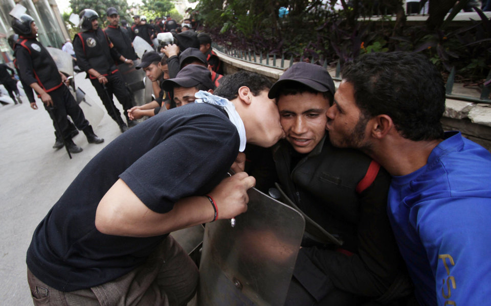 Photo -   Protesters kiss an Egyptian police officer outside the Defense Ministry in Cairo, Egypt, Wednesday, May 2, 2012. Suspected supporters of Egypt's military rulers attacked predominantly Islamist anti-government protesters outside the Defense Ministry in Cairo Wednesday, setting off clashes that left more than ten people dead as political tensions rise three weeks before crucial presidential elections. (AP Photo)