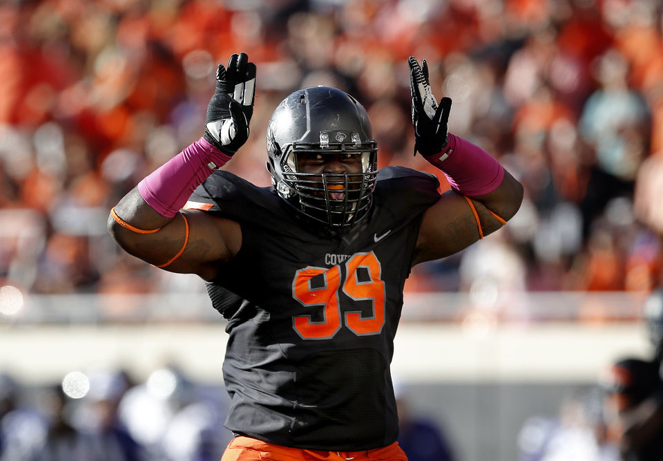 Photo - CELEBRATION: Oklahoma State's Calvin Barnett (99) celebrates a tackle in the third quarter during the second half of a college football game between the Oklahoma State University Cowboys (OSU) and the Kansas State University Wildcats (KSU) at Boone Pickens Stadium in Stillwater, Okla., Saturday, Oct. 5, 2013. OSU won 33-29.Photo by Sarah Phipps, The Oklahoman