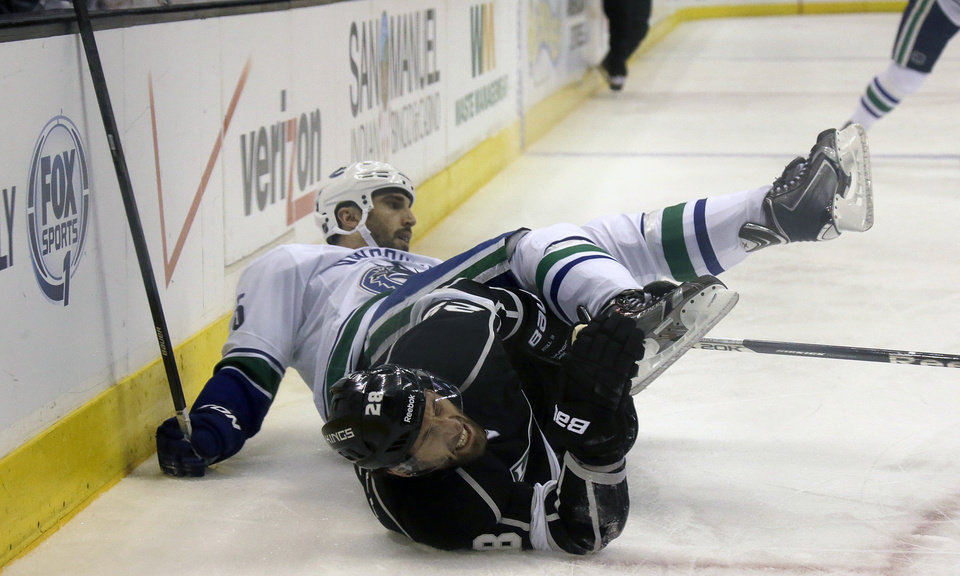 Photo - Vancouver Canucks defenseman Jason Garrison, left, and Los Angeles Kings center Jarret Stoll (28) collide in the first period of an NHL hockey game in Los Angeles, Monday, Jan. 13, 2014.  (AP Photo/Reed Saxon)