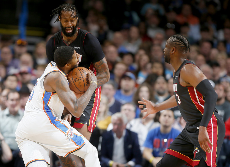 Photo - Oklahoma City's Paul George (13) runs into Miami's James Johnson (16) as Dwyane Wade (3) watches during an NBA basketball game between the Oklahoma City Thunder and the Miami Heat at Chesapeake Energy Arena in Oklahoma City, Monday, March 18, 2019. Miami won 116-107. Photo by Bryan Terry, The Oklahoman