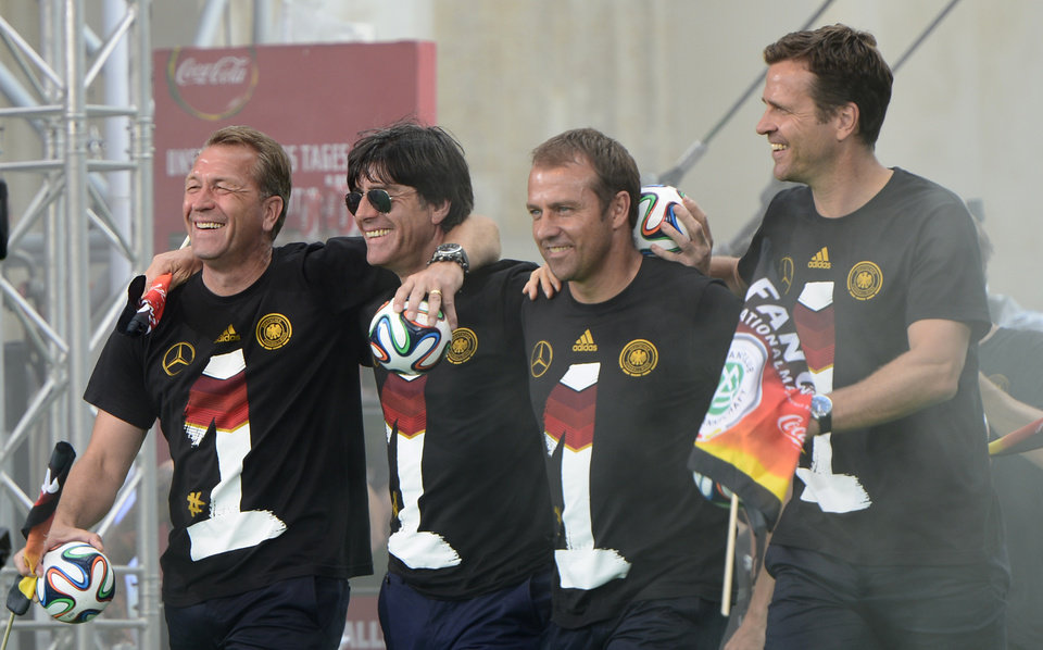 Photo - The German coaching team, from left, goalkeeper coach Andreas Koepke, head coach Joachim Loew, assistant coach Hansi Flick and team manager Oliver Bierhoff walk onto the stage after the arrival of the German national soccer team in Berlin Tuesday, July 15, 2014. Germany beat Argentina 1-0 on Sunday to win its fourth World Cup title.  (AP Photo/Jens Meyer)