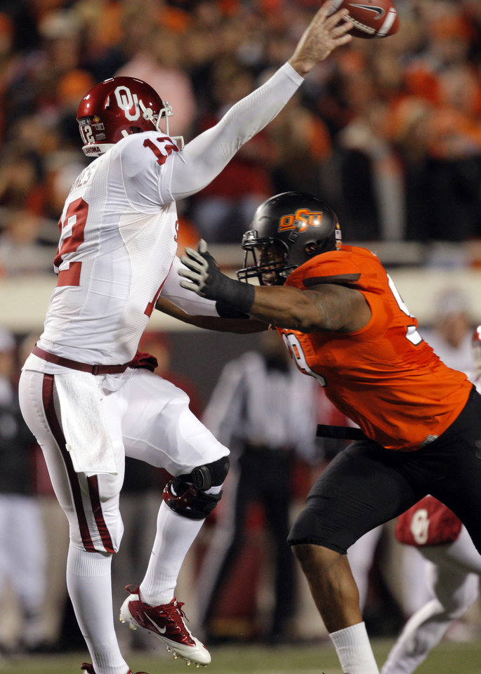 Oklahoma State's Richetti Jones (99) pressures Oklahoma's Landry Jones (12) as he throws the ball during the Bedlam college football game between the Oklahoma State University Cowboys (OSU) and the University of Oklahoma Sooners (OU) at Boone Pickens Stadium in Stillwater, Okla., Saturday, Dec. 3, 2011. Photo by Sarah Phipps, The Oklahoman