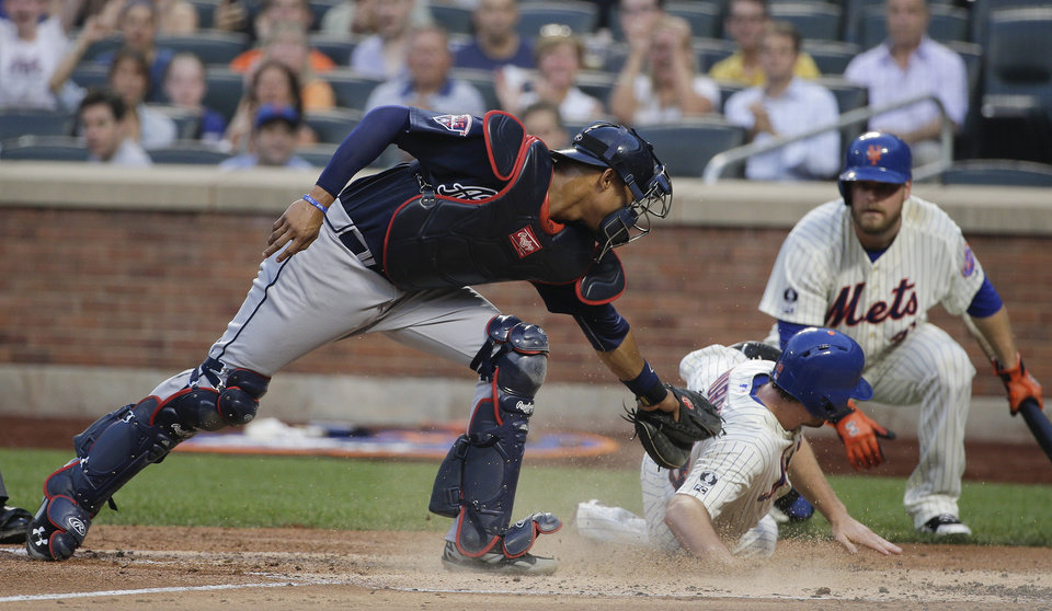 Photo - New York Mets second baseman Daniel Murphy (28) slides safely across home plate for a run ahead of the tag from Atlanta Braves catcher Christian Bethancourt (25) in the third inning of a baseball game, Tuesday, July 8, 2014, in New York. Murphy scored from second on a base hit by David Wright. (AP Photo/Julie Jacobson)