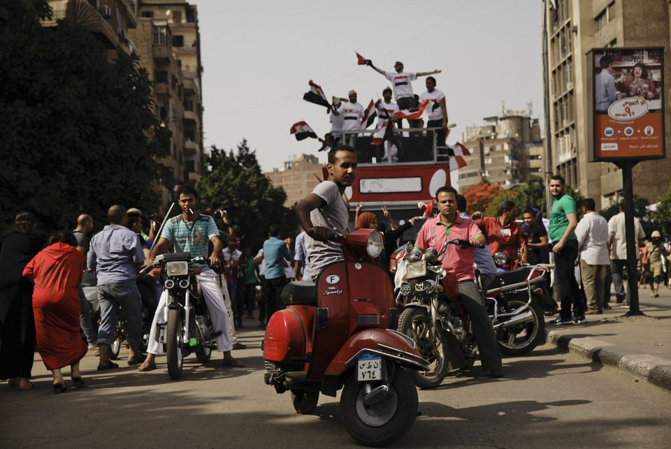 Photo - Supporters of presidential candidate Abdel-Fattah el-Sissi dance and wave national flags during the first day of a presidential election outside a polling site in Cairo, Egypt, Monday, May 26, 2014. El-Sissi's supporters danced to pop tunes praising the military and sported T-shirts bearing his image as they cast ballots Monday in a presidential election that is seen certain to vault the retired field marshal to office. (AP Photo/Nariman El-Mofty)