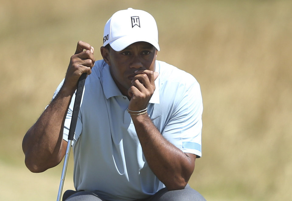 Photo - Tiger Woods of the United States lines up a putt on the 14th green during the second round of the British Open Golf Championship at Muirfield, Scotland, Friday July 19, 2013. (AP Photo/Scott Heppell)
