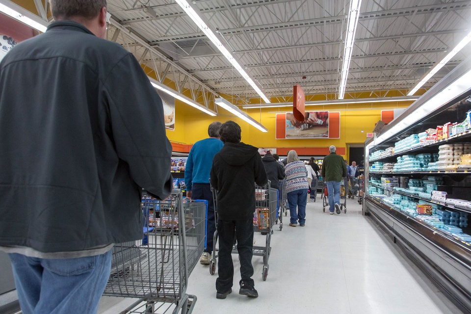 Photo - People wait in a line to stock up on bottled water at a supermarket in Charleston, W.Va. on Saturday, Jan. 11, 2014 in the wake of Freedom Industries' chemical spill into the Elk River on Thursday. Customers were allowed to purchase up to four cases of water at a time. As many stores ran out, the West Virginia National Guard was sent to bring bottled water to local distribution centers. (AP Photo/Michael Switzer)