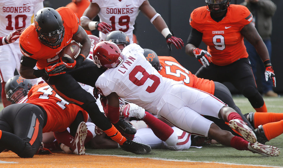 Photo - Oklahoma State's Desmond Roland (26) scores a touchdown past Oklahoma's Gabe Lynn (9) during the Bedlam college football game between the Oklahoma State University Cowboys (OSU) and the University of Oklahoma Sooners (OU) at Boone Pickens Stadium in Stillwater, Okla., Saturday, Dec. 7, 2013. Photo by Chris Landsberger, The Oklahoman