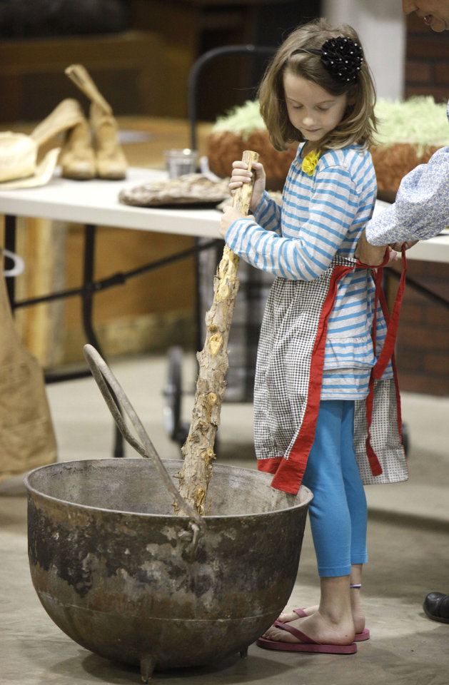 Seven-year-old MiKenna Seale stirs a kettle during a spring break class about life in the 1800s, at the Edmond Historical Society and Museum in Edmond, OK, Tuesday, March 20, 2012,  By Paul Hellstern, The Oklahoman