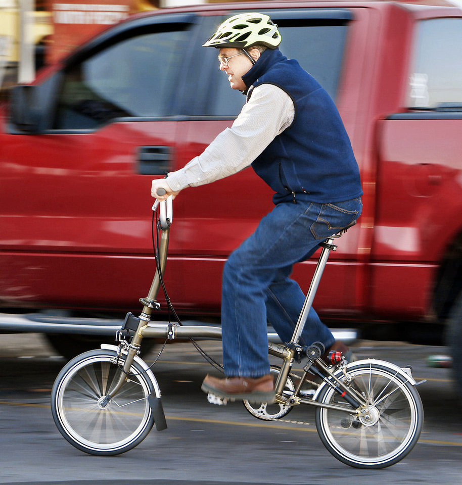 "Photo - Hank Ryan, co-owner of Al's Bicycles, rides a folding bicycle Tuesday. The bike shop specializes in ""folders"" and now carries three  brands.  Photos by STEVE SISNEY, THE OKLAHOMAN"
