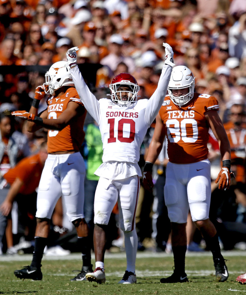 Photo - Oklahoma's Pat Fields (10) celebrates a play in front of Texas wide receiver Collin Johnson (9) and Cade Brewer (80) during the Red River Showdown college football game between the University of Oklahoma Sooners (OU) and the Texas Longhorns (UT) at Cotton Bowl Stadium in Dallas, Saturday, Oct. 12, 2019. OU won 34-27. [Sarah Phipps/The Oklahoman]