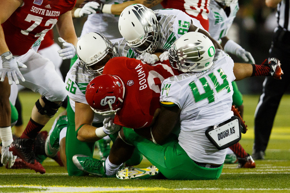 Photo - The Oregon defense stops South Dakota running back Trevor Bouma (21) during the first quarter of an NCAA college football game in Eugene, Ore., Saturday, Aug. 30, 2014. (AP Photo/Ryan Kang)
