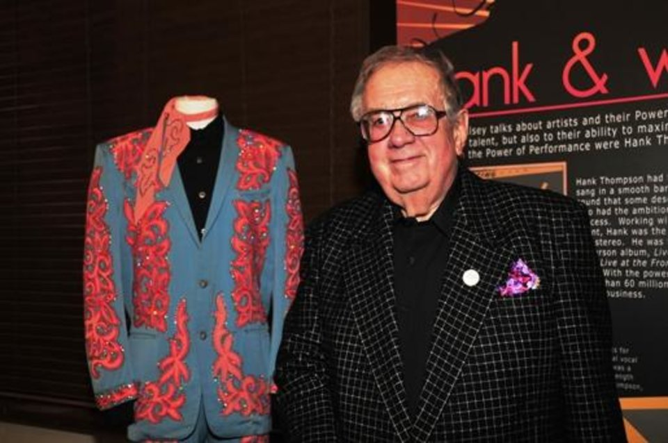 "Music impresario Jim Halsey poses with the late Hank Thompson's Nudie suit at the January opening event for the exhibit ?Starmaker: Jim Halsey and the Legends of Country Music"" at the Gaylord-Pickens Oklahoma Heritage Museum. the exhibit is on view through May 18. Photo by Captured Moments Photography"