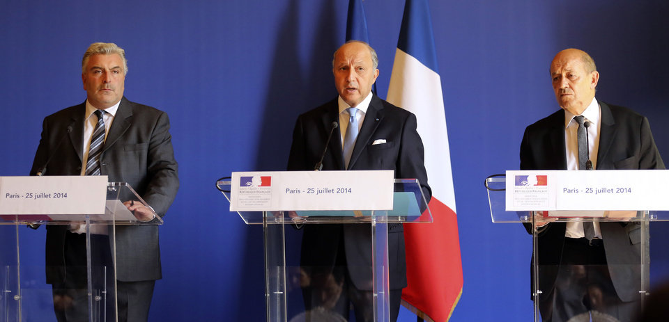 Photo - French foreign minister Laurent Fabius, center, flanked by French defense minister Jean-Yves Le Drian, right, and transport minister Frederic Cuvillier, left,  addresses reporters during a press conference held at the foreign ministry in Paris, Friday July 25, 2014 after a plane crashed in Mali. At least 116 people were killed in Thursday's disaster, nearly half of whom were French. One of two black boxes was recovered from the wreckage in the Gossi region of Mali near the border with Burkina Faso, and was taken to the northern city of Gao, where a French contingent is based.  (AP Photo/Remy de la Mauviniere)