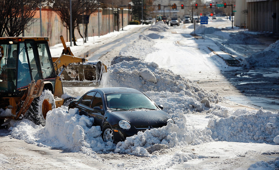 Photo - A front-end loader removes snow around an abandoned car on E.K. Gaylord and Robert S. Kerr. Many spent Christmas Day, Dec. 25, 2009,  digging out from record snow storm that dumped 14 inches of snow in the Oklahoma City area.   Photo by Jim Beckel, The Oklahoman