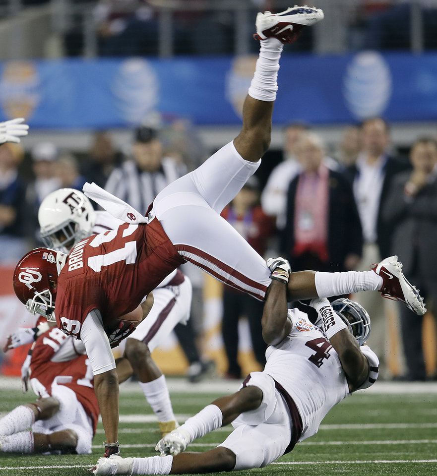 Photo - Texas A&M's Toney Hurd Jr. (4) upends Oklahoma's Justin Brown (19) during the college football Cotton Bowl game between the University of Oklahoma Sooners (OU) and Texas A&M University Aggies (TXAM) at Cowboy's Stadium on Friday Jan. 4, 2013, in Arlington, Tx. Photo by Chris Landsberger, The Oklahoman
