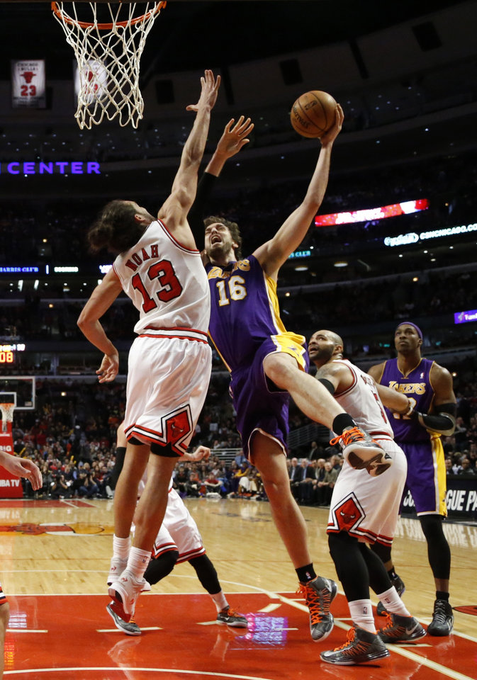 Photo - Los Angeles Lakers forward Pau Gasol (16) shoots between Chicago Bulls center Joakim Noah (13) and Carlos Boozer during the second half of an NBA basketball game Monday, Jan. 21, 2013, in Chicago. The Bulls won 95-83. (AP Photo/Charles Rex Arbogast)