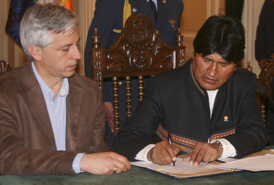 In this photo released by Bolivia's Presidency Press Office, Bolivia's President Evo Morales signs a decree allowing the takeover of shares in Empresa de Electricidad de La Paz (Electropaz) and Empresa de Luz y Fuerza de Oruro (Elfeo), Vice President Alvaro Garcia Linera at the government palace in La Paz, Bolivia, Saturday, Dec. 29, 2012. The decree read by Morales also calls for Iberdrola to receive indemnification after an independent firm is hired within 180 days to determine the value of the nationalized shares. Bolivia's Vice President Alvaro Garcia Linera is pictured at left. (AP Photo/Presidency Press Office, Jose Lirauze)
