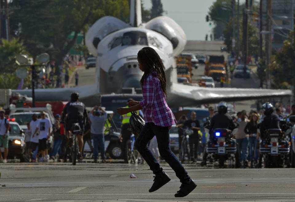 Photo -   A young woman runs across the street in front of the space shuttle Endeavour as it is slowly moved down Crenshaw Blvd., Saturday, Oct.13, 2012, in Los Angeles. The shuttle is on its last mission — a 12-mile creep through city streets. It will move past an eclectic mix of strip malls, mom-and-pop shops, tidy lawns and faded apartment buildings. Its final destination: California Science Center in South Los Angeles where it will be put on display. (AP Photo/Mark J. Terrill)