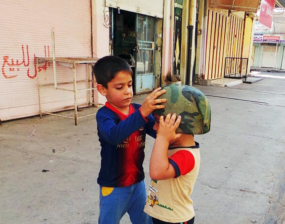 Photo - Children play with an Iraqi Army helmet left behind after militants from the al-Qaida-inspired Islamic State of Iraq and the Levant (ISIL) took over the northern city of Mosul, Iraq, Friday, June 13, 2014. Iraqi officials say al-Qaida-inspired militants who this week seized much of the country's Sunni heartland have pushed into an ethnically mixed province northeast of Baghdad, capturing two towns there. The writing on the metal shutters at left advertises a shop for sale. (AP Photo)