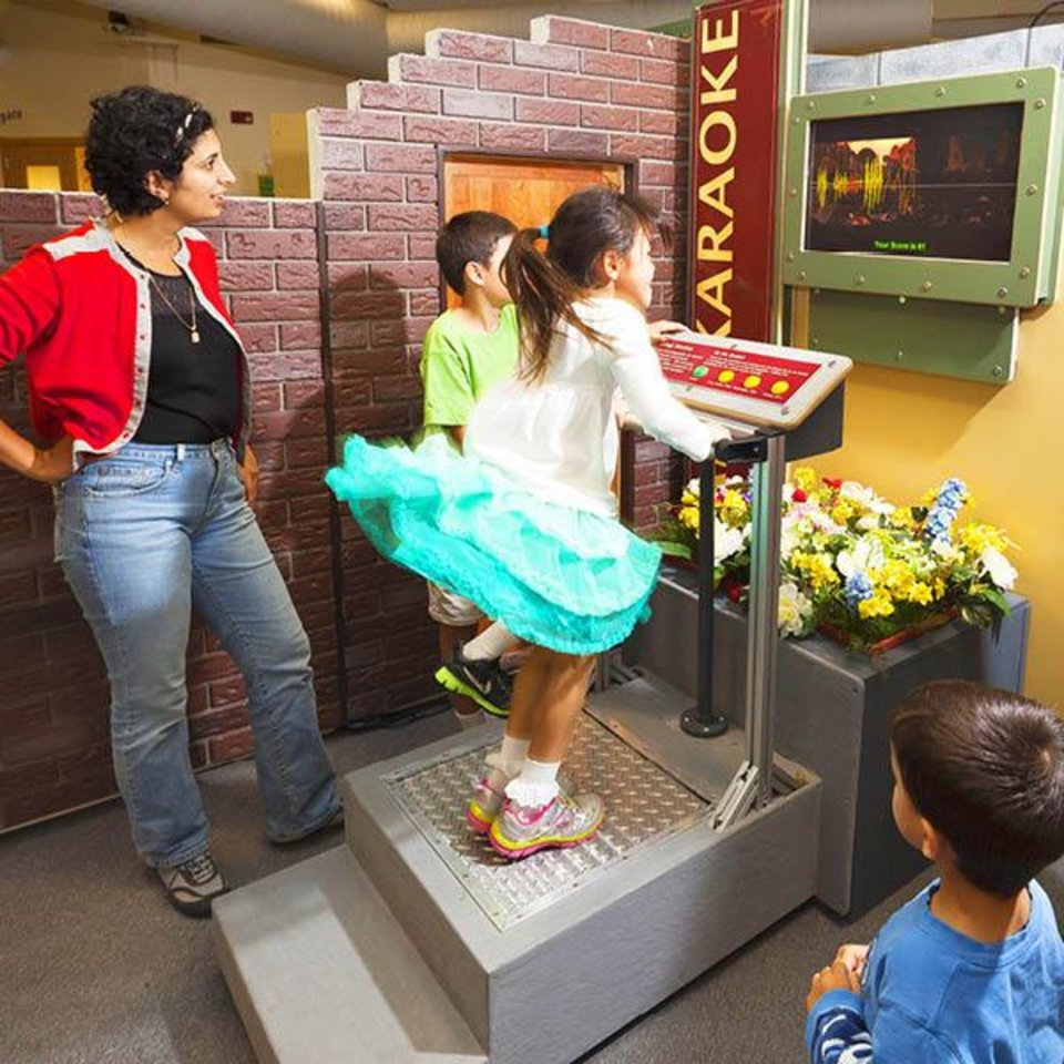 Photo -  A child jumps on a platform to simulate an earthquake in an interactive display that is part of the traveling exhibition