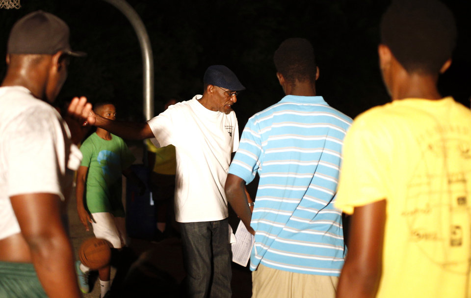 Photo - David m, middle, coaches youth during midnight basketball at Christ Temple Community Church in Oklahoma City, Friday, July 25, 2014. Photo by Sarah Phipps, The Oklahoman